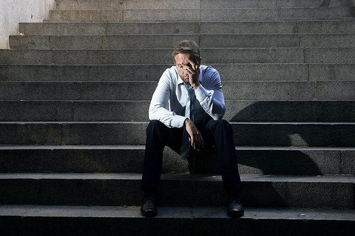 businessman crying lost in depression sitting on street concrete
