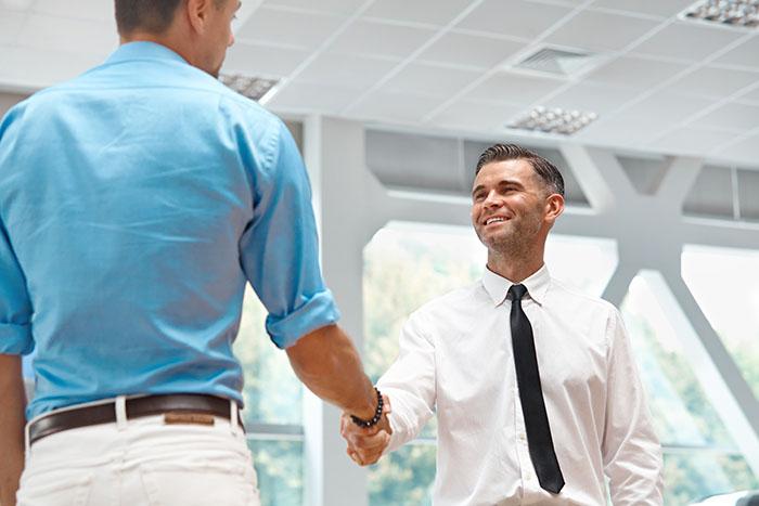 Car Salesman Invites Customers at Showroom.